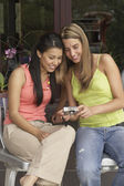 Two young women reviewing digital photos — Stock Photo
