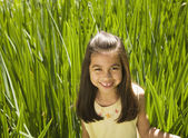 Young Hispanic girl in tall grass — Stock Photo