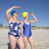 Two senior women in bathing suits shading their eyes at beach — Stock Photo