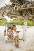 Young girls sitting in lawn chair on the beach — Stock Photo