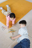 Boy and girl playing pick up sticks — Stock Photo