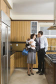 Hispanic parents with baby in kitchen — Stock Photo