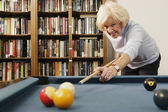 Elderly woman shooting pool — Stock Photo