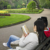 Couple looking at map on park bench — Stock Photo