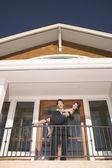 Portrait of man holding woman on balcony — Stock Photo
