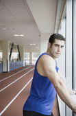 Man next to window of indoor track — Stock Photo