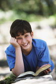 Boy smiling with book outdoors — Stock Photo