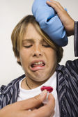 Sick boy being given cough syrup — Stock Photo