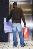 African man waiting for elevator with shopping bags — Stock Photo