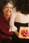 Hispanic granddaughter giving grandmother gift — Stock Photo