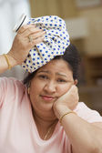 Woman holding a cold compress on her head — Stock Photo