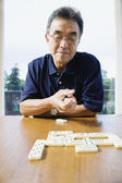 Senior man playing dominos — Stock Photo