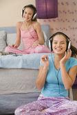 Hispanic sisters listening to music on headphones — Stock Photo