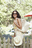 Young woman holding a bag and smiling for the camera — Stock Photo