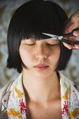Asian woman having bangs trimmed — Stock Photo