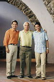 Three generations of men posing for the camera — Stock Photo