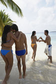 South American couples walking on beach — Stock Photo
