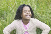 Young girl sitting on grass smiling looking at camera — Stock Photo