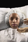 African American woman in hospital cap and gown with gloved hands reaching for her — Stockfoto