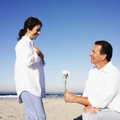 Hispanic man giving flower to wife — Stock Photo