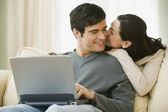 Pareja hispana abrazando y uso del ordenador portátil — Foto de Stock
