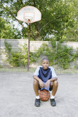 Young boy sitting on basketball — Stock Photo