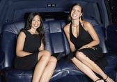 Two woman in formal outfits in backseat of car — Stock Photo