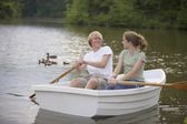 Teen couple rowing boat — Stock Photo