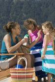 Mère, application de lotion solaire aux filles sur la plage — Photo