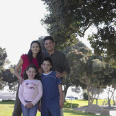 Family posing for the camera in park — Stock Photo
