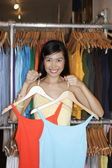 Portrait of woman holding up two shirts — Stock Photo