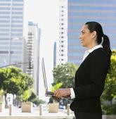 Hispanic businesswoman holding laptop — Stock Photo