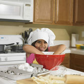 Young Hispanic girl with hands in mixing bowl in kitchen — Stock Photo