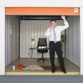 Businessman getting ready to sleep in storage unit office — 图库照片