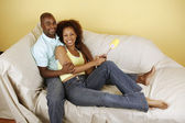 Couple on couch with paint roller — Stock Photo