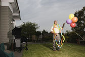 Portrait of elderly man wearing birthday hat and streamers and holding balloons — Stock Photo