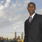 African businessman with urban skyline in background — Stock Photo