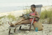 Senior woman reading on beach in lounge chair — Stock Photo