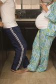 Pregnant couple in pajamas in kitchen — Stock Photo