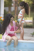 Mother applying lotion to daughter's leg at side of pool — Stock Photo