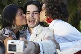 Man taking photograph of two women kissing him — Stock Photo