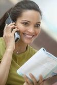 Woman reading magazine and talking on telephone — Stock Photo
