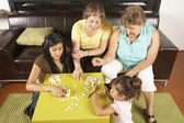 Female members of a family playing dominoes — Photo