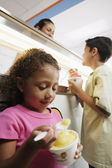 Brother and sister eating ice cream in ice cream shop — Stock Photo