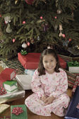 Hispanic girl surrounded by Christmas gifts — Stock Photo