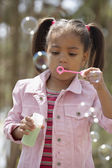 African American girl blowing bubbles — Stock Photo