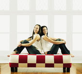Two young women sitting back to back — Stock Photo