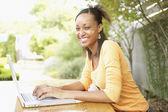 Portrait of teenage girl typing on laptop — Stock Photo