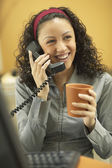 Young businesswoman drinking coffee and talking on the phone — Stock Photo