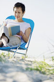 Woman in lounge chair reading book — Stock Photo